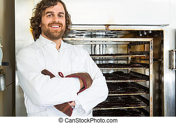 Portrait of happy male butcher standing arms crossed by oven at shop