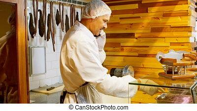 Butcher talking on mobile phone 4k - Butcher talking on ...