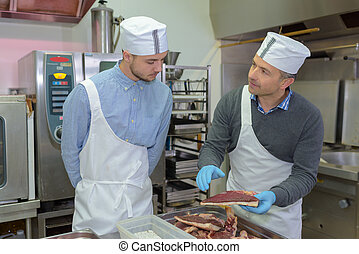 Butcher talking to trainee