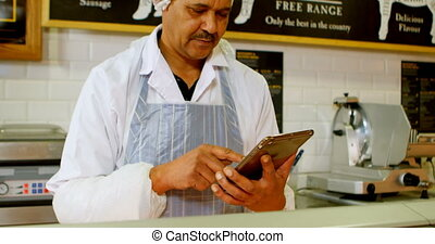 Butcher using digital tablet in shop 4k - Attentive butcher...