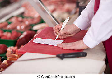 Butcher Writing On Paper At Counter