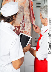 Butchers Analyzing Meat Hanging In Butchery