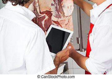 Butchers Holding Digital Tablet In Meat Shop