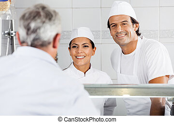 Butchers Looking At Customer In Store