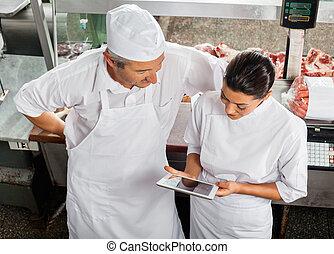 Butchers Using Digital Tablet In Store
