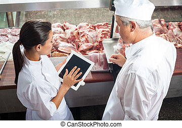 Butchers Using Digital Tablet In Store