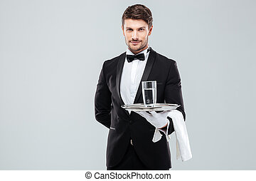 Butler in gloves holding glass of water on silver tray