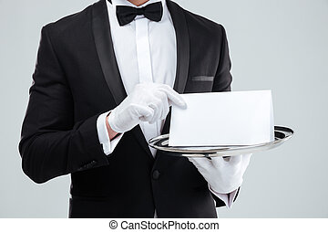 Butler in tuxedo and gloves holding blank card on tray -...