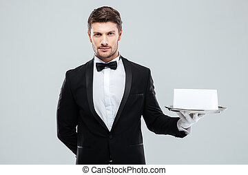 Butler in tuxedo and gloves holding tray with blank card -...