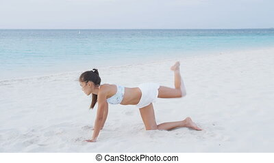 Butt and glute exercise with fitness woman doing Fire Hydrant variation. Fire Hydrant With Crossover Donkey Kick. Fit female model exercising buttocks, glutes and legs on beach. RED EPIC.