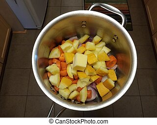 butter and carrots and squash and onions in metal pot in kitchen