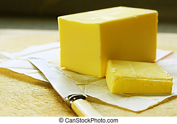 Butter - Block of butter, cut, on old chopping board, with ...