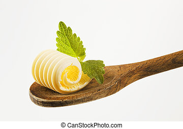 Butter curl on a wooden spoon - Closeup of butter curl on a...