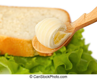Butter curl on spoon with bread on background - Butter curl...