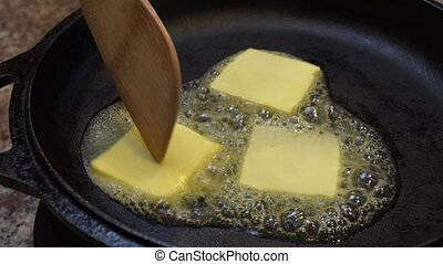 Butter melting in cast iron frying pan from side view.
