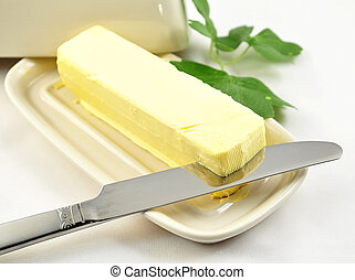 butter on white butterdish with knife , close up