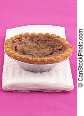 Butter tart on white napkin and deep pink tablecloth