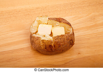 Buttered Baked Potato on Wood Board