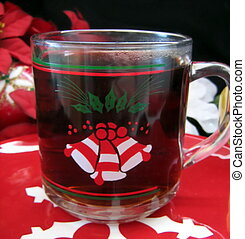 A cup of hot Christmas coffee with rum. Red Christmas plate and red and white background.