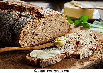 Buttered slice of rye bread with crusty loaf