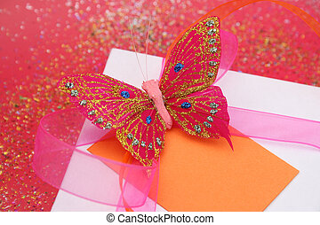 Pink butterfly on a white gift box as a decoration