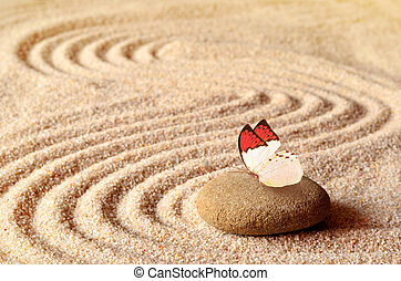 Butterfly on a zen stone with circle in the sand.