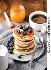Buttermilk pancakes with blueberries, honey and cup of coffee