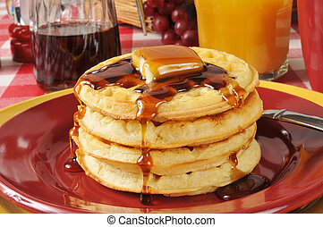 A stack of buttermilk waffles with butter and maple syrup
