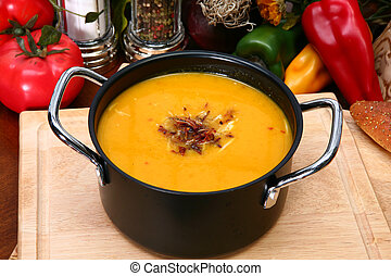 Small pot of butternut squash soup sprinkled with toasted coconut.