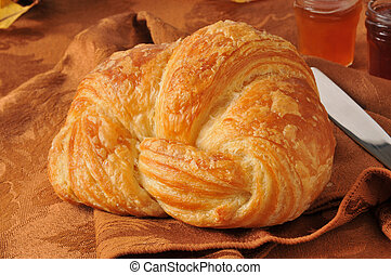 A large golden buttery croissant with jams