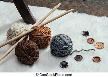button and woolen yarn ball on carpet, handmade
