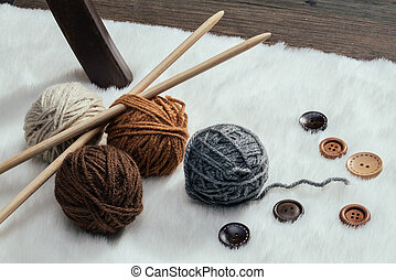 button and woolen yarn ball on carpet, handmade