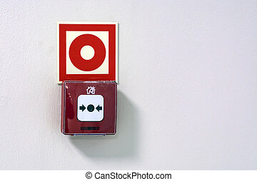button fire alarm on a white wall in the supermarket.