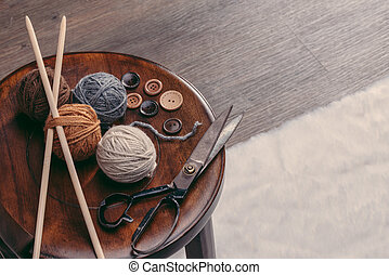 button, scissors and yarn ball on wooden chair, handmade