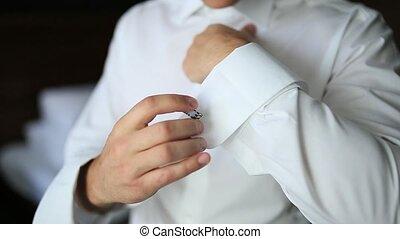 Buttoning cuffs. The groom wears cufflinks. Businessman...