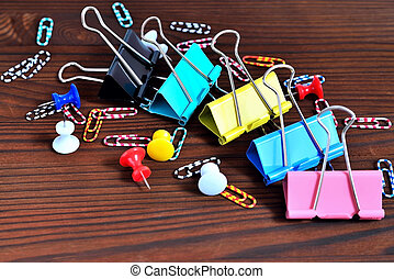 Buttons, colored paper clips, paper clips on a natural brown background
