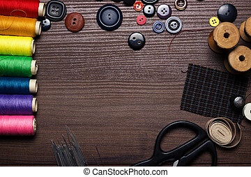 buttons, needles and multicolored threads on the wooden ...