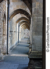 Arches under the huge stone buttresses of the Southern wall of Winchester Cathedral, Hampshire.