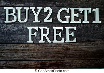 Buy 2 Get 1 Free with space copy on wooden background