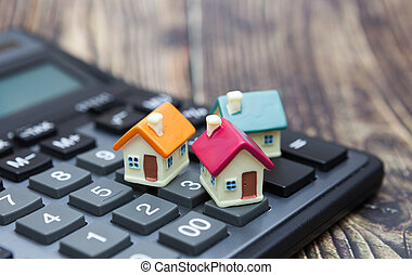 Buy home. House is placed on the calculator. Planning savings money of coins to buy a home concept for property, mortgage and real estate investment.