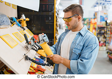 Buyer holding edging machine in hardware store