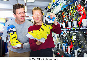 Buyers are choosing boots for skiing in store.