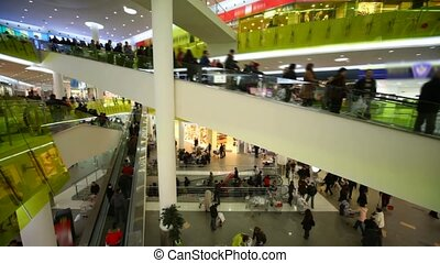 buyers crowd rushing on escalators in big multistorey mall shop