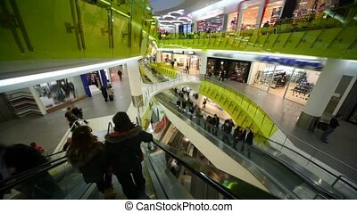buyers going in mall, camera moving down on escalator