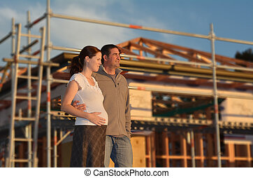Buying a new house - Concept - Young couple hugging outside...