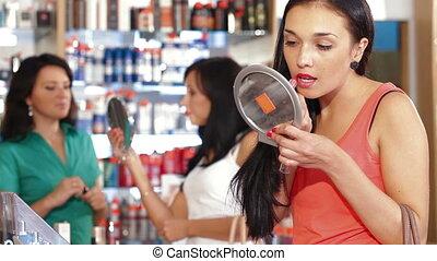 Buying Cosmetics - Young woman choosing and buying cosmetics...