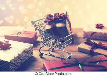 buying gifts - wrapped present in shopping cart on bokeh background