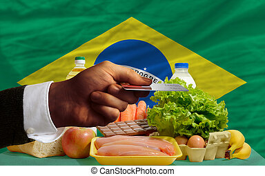 man stretching out credit card to buy food in front of complete wavy national flag of brazil