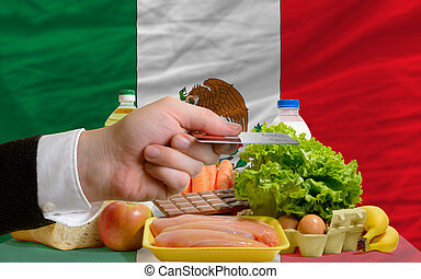 man stretching out credit card to buy food in front of complete wavy national flag of mexico