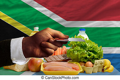 man stretching out credit card to buy food in front of complete wavy national flag of south africa